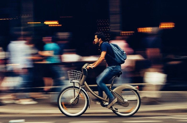 man riding a bicycle down a street